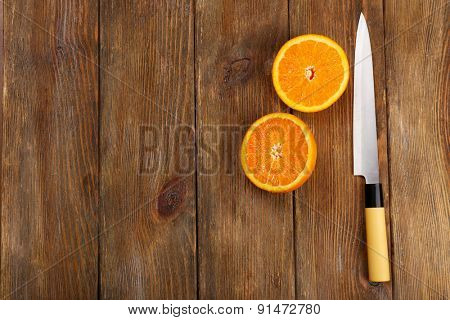 Halves of orange with knife on wooden background