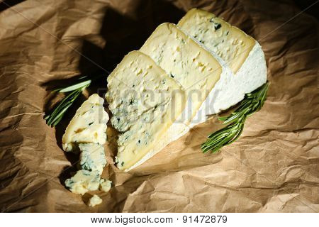 Pieces of tasty blue cheese with rosemary on paper background
