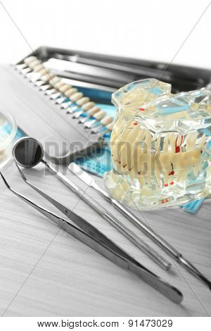 Fake teeth, prosthesis and dental instruments on table background