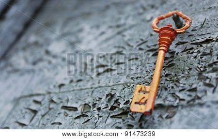 Old key on wooden antique door close-up