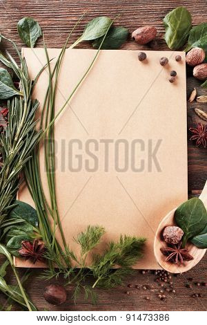 Recipe book page with different herbs on wooden background