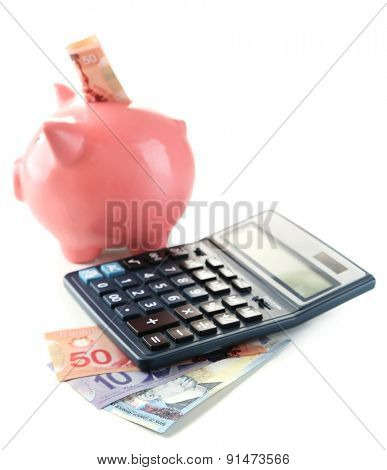 Calculator and piggy bank with Canadian dollars, isolated on white