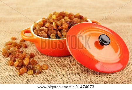 Raisins in pan on sackcloth, closeup