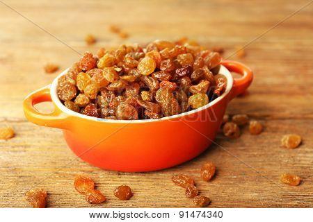 Raisins in pan on wooden table, closeup