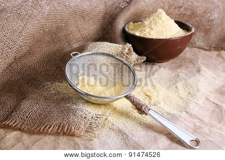 Flour in bowl with sieve on burlap cloth background