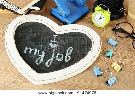 Inscription on blackboard I love my job on workplace