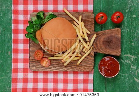 Hamburger, french fries and vegetables on wooden table top view