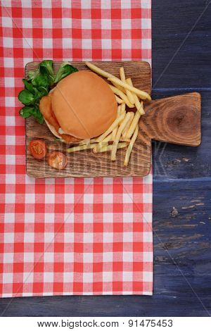 Hamburger, french fries and tomato on wooden table top view