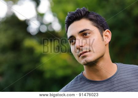 Portrait of handsome brunet young man in casual clothing in the park