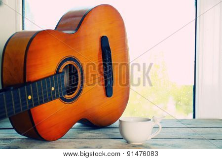 Acoustic guitar and cup of tea next the window with rain drops
