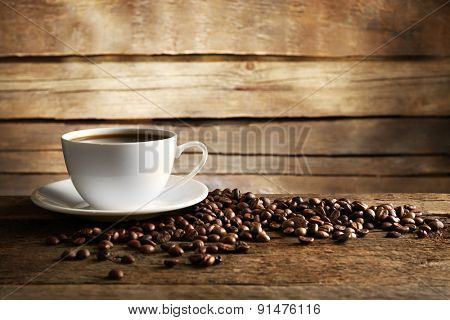Cup of coffee with grains on wooden background