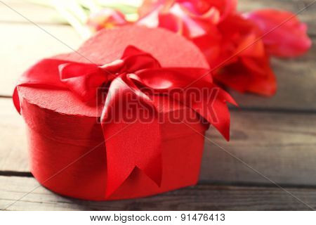 Heart shaped Valentines Day gift box with tulips on wooden table