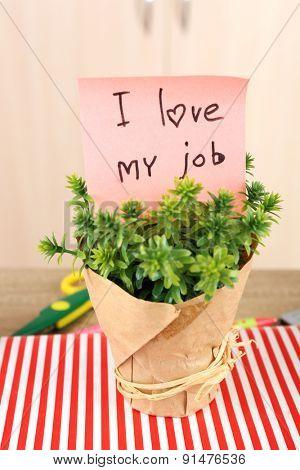 Inscription I love my job in flowerpot on workplace