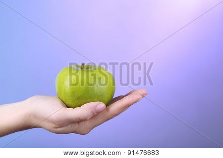 Female hand with apple on colorful background