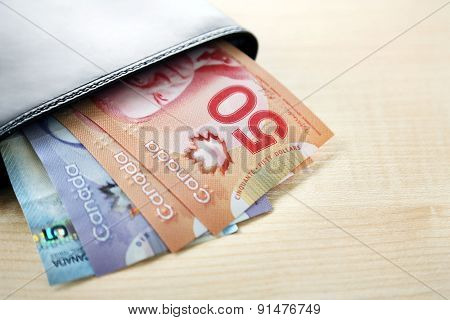 Male wallet with Canadian dollars on wooden table