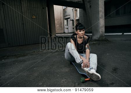 black haired tattooed lady sitting on longboard in backyard