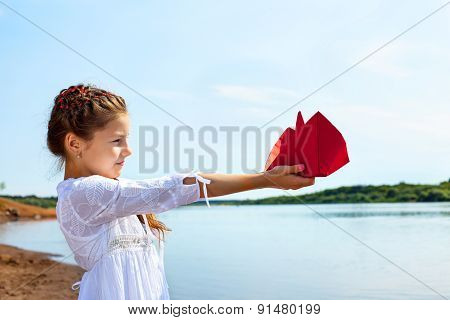 Adorable little girl holding red paper boat