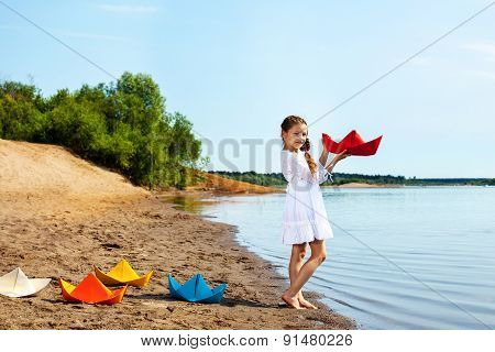 Pretty girl and colorful paper boats in park