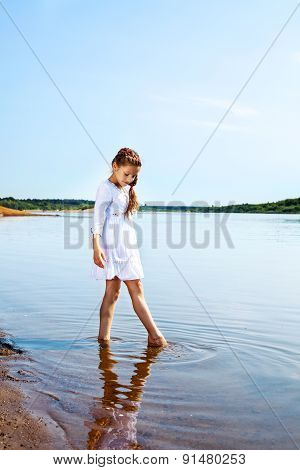 Cute little girl resting in park by lake