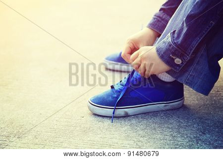 closeup of skateboarder hands tying shoelace outdoor