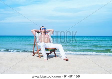 Young, fit and handsome man with athletic and muscled body chilling in a beach chair at summer
