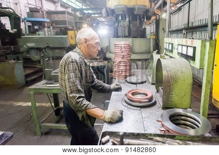 Senior worker checks balancing of detail
