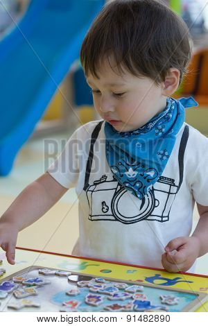 Cute Young Boy Making A Puzzle