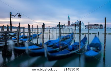 Venice, Italy - 20 May 2105: Gondolas Moored On The Lagoon, With The Church Of San Giorgio Maggiore