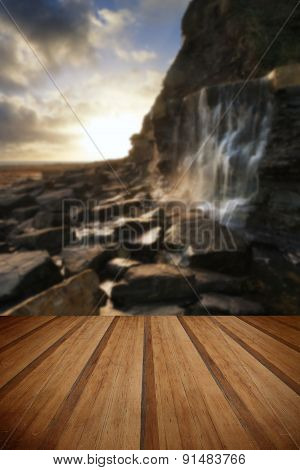 Beautiful Landscape Image Waterfall Flowing Into Rocks On Beach At Sunset With Wooden Planks Floor