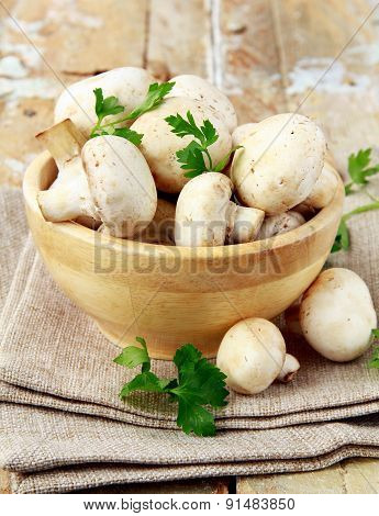 Fresh champignon mushrooms in a wooden bowl