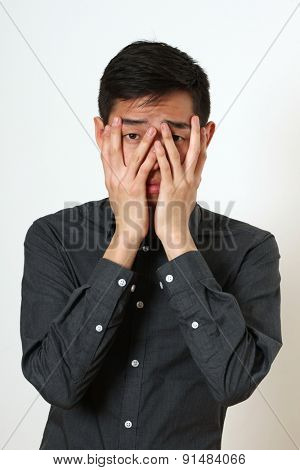 Frustrated young Asian man covering his face with palms.