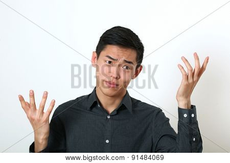 Displeased young Asian man gesturing with two hands.