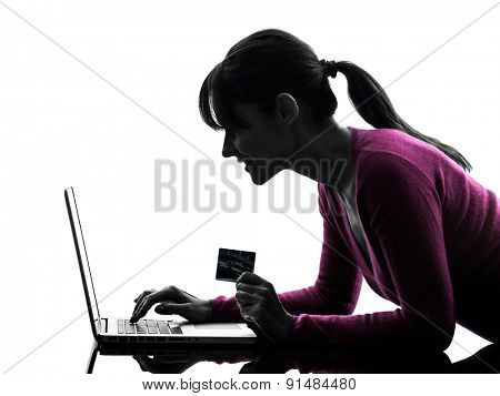 one  woman holding credit card computing laptop computer in silhouette studio isolated on white background