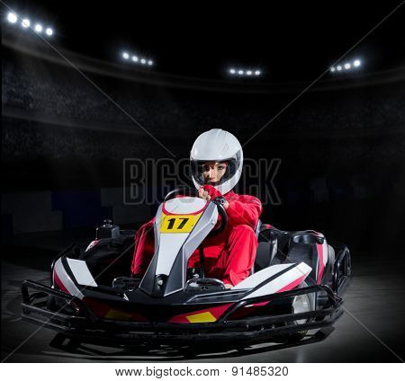 Young girl karting driver at sports hall