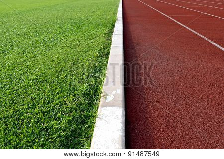 white line between green grass football field and track runway