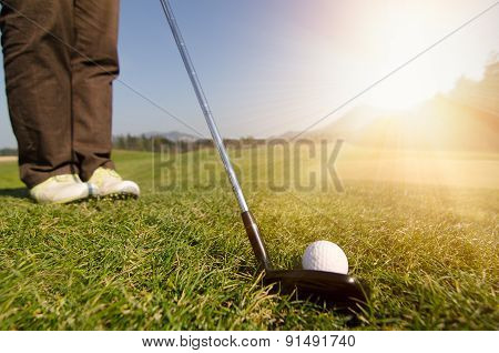 Golfer is chipping a golf ball onto the green with driver golf club.