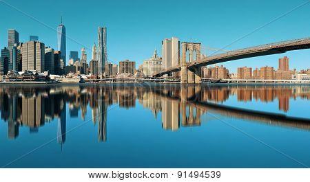 Manhattan financial district with skyscrapers and Brooklyn Bridge reflections.
