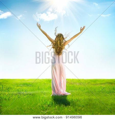 Beauty Girl enjoying nature on the field. Beautiful slim Woman Outdoor raising hands in sunlight rays. Full length Model portrait in long dress. Grassland, Sun Light. Free Lady. Health care concept