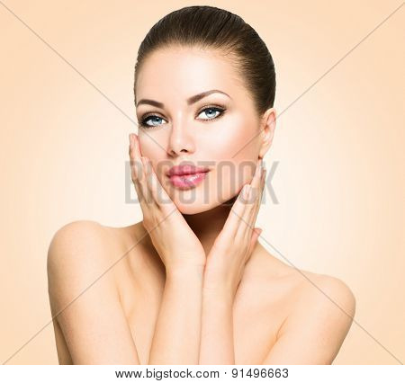 Beauty Portrait. Beautiful Spa Woman Touching her Face. Perfect Fresh Skin. Beauty brunette Model. Youth and Skin Care Concept. Studio shot over beige background