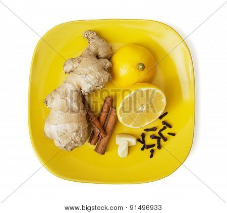 Ginger, Cinnamon, Lemon, Garlic And Cloves On The Yellow Plate