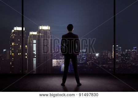 Man Standing In His Office Looking At The City At Night