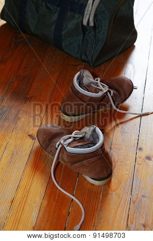 Pair Of Old Shoes And Bag On The Floor