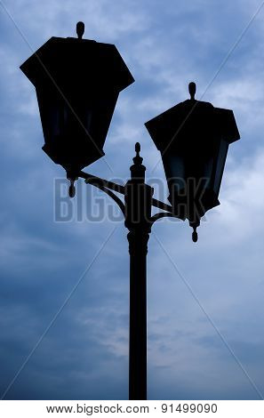 Silhouette Of A Street Lamp In The Background Of A Stormy Sky.