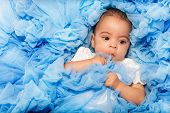 picture of babygro  - Chubby African small baby laying on the blue cloth close - JPG