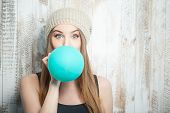 picture of blowing  - Pretty hipster woman is inflating colored balloon - JPG