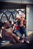 image of beret  - sad girl in a pink beret sits on a parapet with big toy a bear - JPG