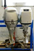 stock photo of outboard engine  - two outboard motors in a repair shop - JPG