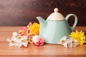 picture of teapot  - Light blue teapot with flowers on a wooden background - JPG