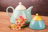 image of teapot  - Light blue teapot with flowers on a wooden background - JPG