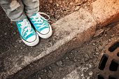 picture of snickers  - Teenager feet in jeans and blue shoes stand on the street edge urban walking theme - JPG